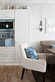 Comfortable dining area with simple, upholstered furnishings and floral scatter cushions in kitchen-dining room; reflections in oven door integrated into fitted cupboards