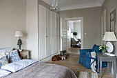 Classic bedroom in white and natural shades with blue accents; view over bed to fitted wardrobes and dining area in adjoining room