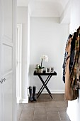 Tray table and wellingtons in hallway of period apartment; clothing hanging from coat rack to one side