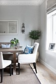 Classic theme; upholstered chairs with blue-pattered scatter cushions at dining table in renovated period apartment with stucco frieze