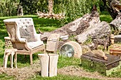 Small items of vintage furniture, armchair, tree stump stool and candlestick on summery lawn
