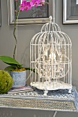 Chrystal chandelier in old birdcage on delicate, wire mesh side table