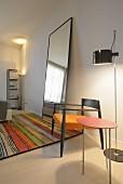 Filigraner Beistelltisch mit roter Platte und Armlehnstuhl mit orangem Polsterbezug vor Stehleuchte, daneben Standspiegel auf buntem Streifenteppich in minimalistischem Ambiente