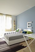 Twin beds with white frames and headboards against pastel blue wall in modern interior