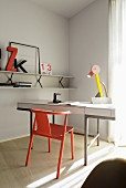 Red classic wooden chair at white writing desk with postmodern table lamp; white shelf on wall painted pale grey