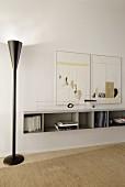 Modern standard lamp in black metal next to white floating shelf on wall below artworks in minimalist interior