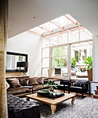Rustic wooden coffee table, grey-brown velvet sofa and black armchairs under large skylight
