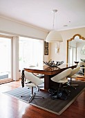 White swivel chairs and solid-wood table under white pendant lamp in front of mirror with curved gilt frame in minimalist traditional interior