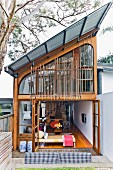 House with monopitch roof, glass and wood structure and view of daybed in interior through open folding terrace doors