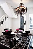 Classic armchairs made from metal slats around white Tulip Table on black and white patterned rug under chandelier next to staircase