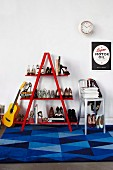Guitar leaning against red ladder shelves of ladies' shoes and metal bar stool on rug with blue geometric pattern below poster on white wall