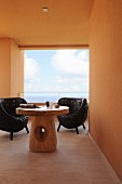 Black wicker chairs and mushroom-shaped, solid wooden table on roofed terrace; sea view through glass balustrade