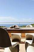Holztisch und Pantonstühle auf sonniger Terrasse mit Meerblick