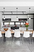 Open-plan kitchen with long table and shell chairs below simple pendant lamps