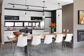 Dining table with 10 light shell chairs in front of modern, white fitted kitchen