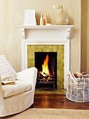 Hussensessel und Brennholzkorb vor loderndem Kaminfeuer; weiss eingeschlagene Bücher und Vasen auf Kaminsims