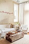 Schrift-Installation an sandfarbiger Wand über Sofa mit weisser Husse und Ottomane mit Tierfellbezug