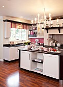 Black and white fitted kitchen with striped Roman blind and pink splashback