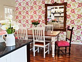 Dining room with floral wallpaper and antique chair with pink seat cushion