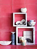 China and ceramic pots in and on stone frames against deep pink wall tiles