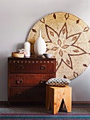 Ethnic arrangement in natural shades - chest of drawers with perforated front, wooden stool and painted picture on wicker disc