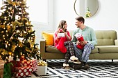 Junges Paar mit Nikolausstrümpfen auf dem Sofa sitzend