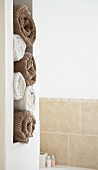 White and brown rolled towels in masonry niche in bathroom