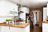 Modern, white fitted kitchens with wooden work surfaces; woman opening microwave