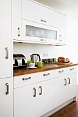 White fronts with robust, U-shaped handles and exotic wood work surface in modern fitted kitchen
