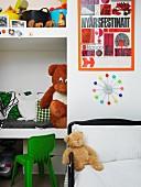 Kinderbett vor Wand mit Uhr, daneben eingebaute Regalböden mit Kissen und Spielsachen in Wandnische