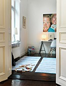 Open double doors leading to boy's room; train set on rug and painting on wall above desk