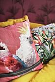 Cushions with colourful bird motifs on sofa
