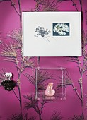 Ceramic sculpture, plexiglas box and picture on wall with mauve wallpaper