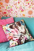 Scatter cushion with vintage photo print on turquoise sofa against pink floral wallpaper