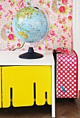 Globe lamp on white, retro sideboard with yellow-painted cupboard doors and red and white polka-dot suitcase to one side