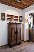 Objets d'art in framed glass cases on wall above old farmhouse cupboard in living area of restored chalet