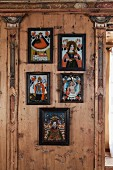 Framed religious folk art between pilasters on artistically wood-panelled wall