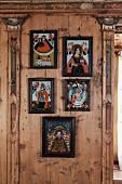 Gerahmte Folklorebilder zwischen kunstvoll verzierten Lisenen auf holzvertäfelter Wand