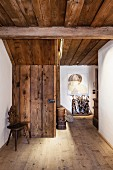 Antique plank chair in rustic hallway of restored farmhouse; contemporary painting above traditional umbrella stand in background
