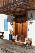 Schlitten, Laternen und Stern-Deko vor der Haustür eines historischen italienischen Chalets