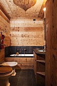 Wooden walls, ceiling and furnishings combined with black slate tiles in rustic, modern bathroom