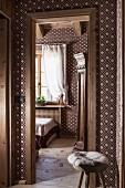 Blick vom Flur in Gästezimmer mit braun-weißer Textiltapete und geometrischem Muster