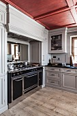 Large kitchen range in pale grey country-house kitchen with coffered ceiling