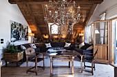 Tisch mit kunsthandwerklich gearbeiteten Stühlen und imposanter Kronleuchter im Hauptraum unterm Dach