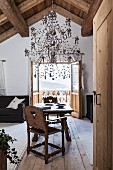 Silver chandelier sculpture above rustic seating area and view of Alpine landscape through open balcony doors