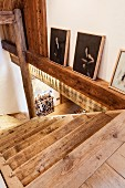 Head of rustic staircase and collection of contemporary, Chinese artworks (by Zeng Fanzhi) to one side leaning against wall