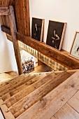 Rustikaler Treppenabgang und seitlich an der Wand aufgestellte Sammlung moderner, chinesischer Kunstbilder (Zeng Fanzhi)