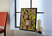 Hand-crafted Advent calender in picture frame with small parcels on green background next to candles on windowsill
