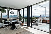 Seating area with delicate, white metal chairs and arc lamp in conservatory with open sliding door leading to roof terrace with view of city
