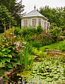 View across pond with flowering pond plants to wooden summer house with lattice windows in idyllic garden